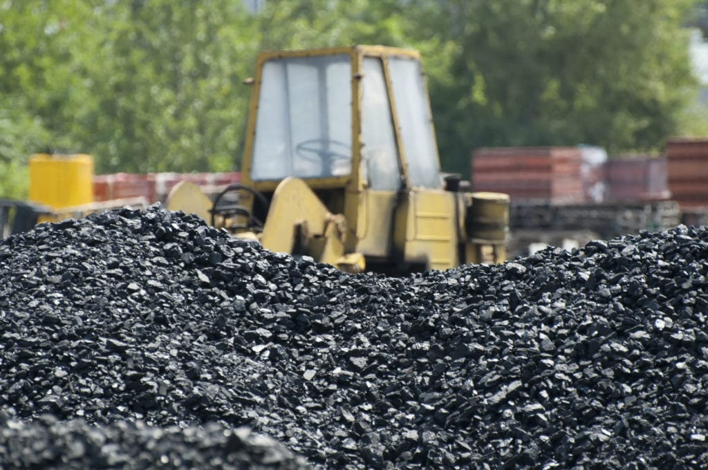 Excavator and coal piles to illustrate Fly ash in concrete